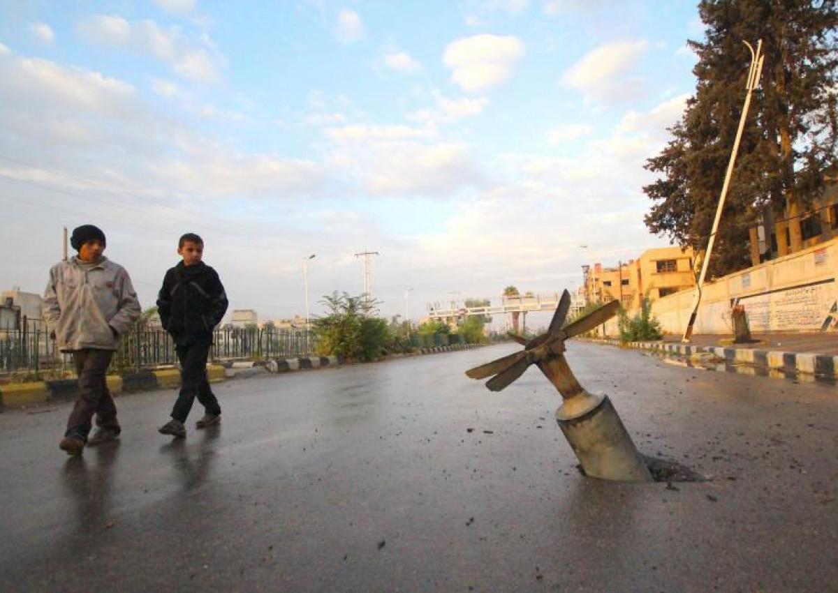 Zwei Jungen laufen an einer Bombe vorbei, die im Boden steckt